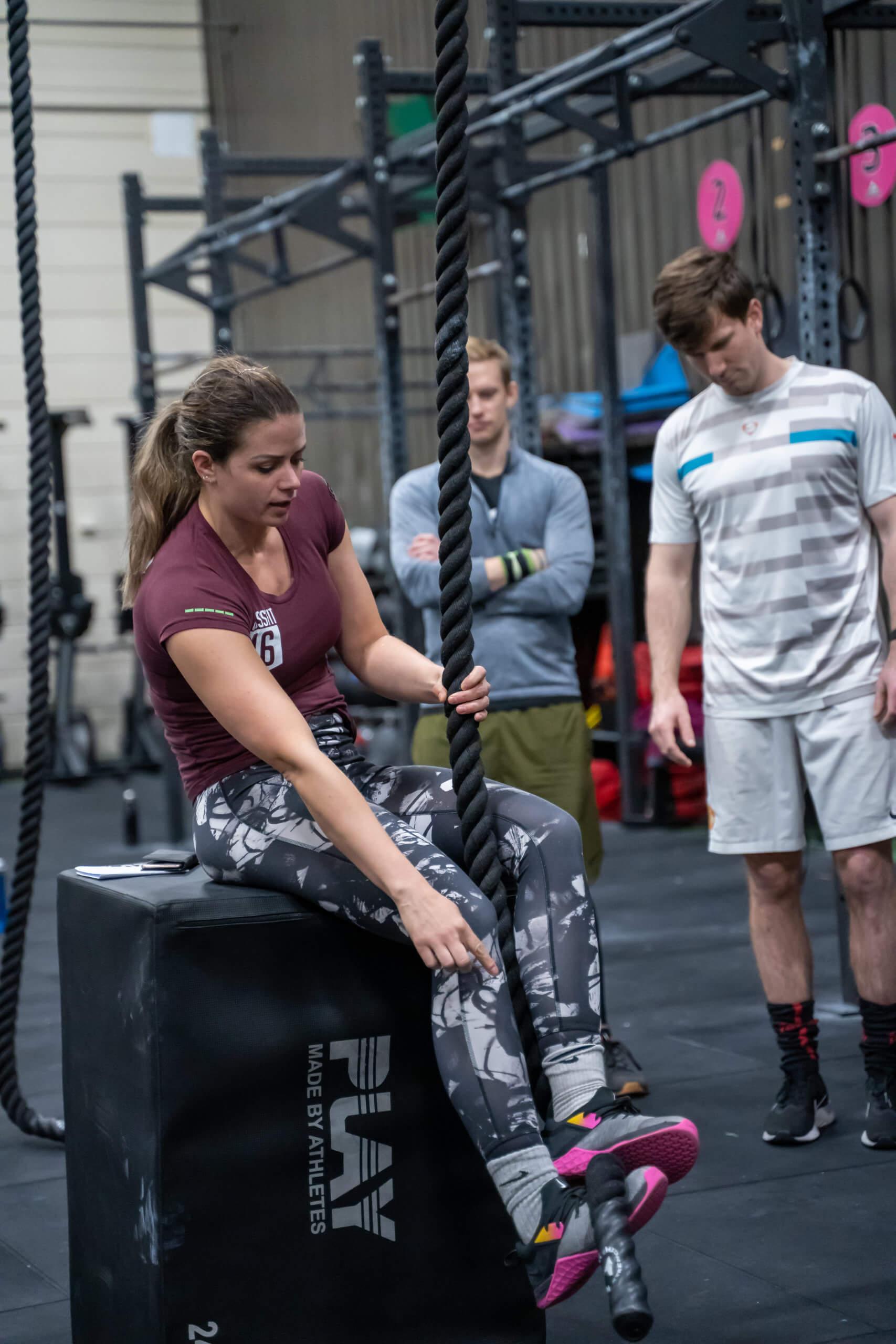 Personlig trener med burgunder tskjorte, grå/hvit kamuflasjetights sitter på en boks fremst og peker ned på bakken. To utøvere bak ser på samme område.