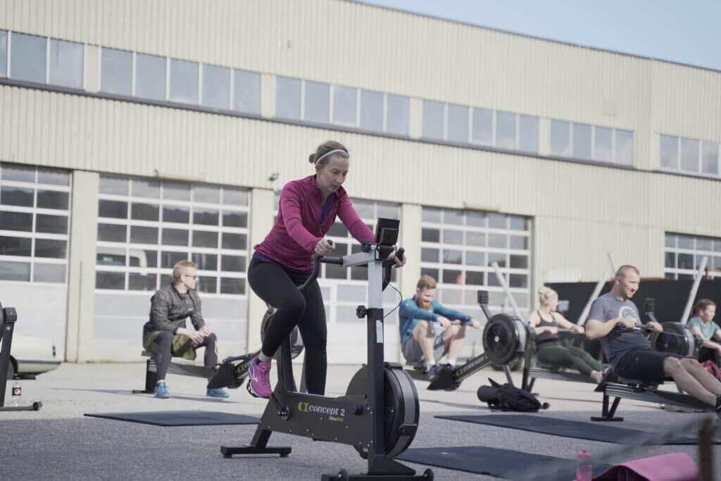 Crossfit 46 utøver med lilla treningsgenser, svarte tights og rosa sko bruker sykkelmaskin for å varme opp. Bak henne er flere crossfit utøvere som bruker romaskinen. På bakken er det plassert yogamatter.