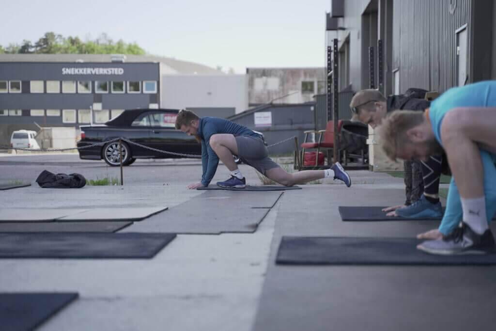 Utøver med mørkeblå treningsgenser og grå shorts tøyer ut på en tøyematte på utsiden av crossfit 46