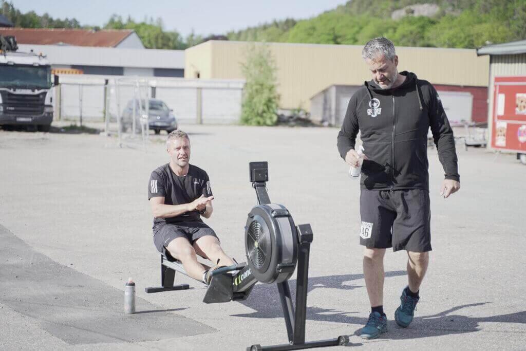 Personlig trener med svart treningsgenser, shorts og blå sko står med en antibac som han har gitt til en av utøverne i bildet. Utøveren sitter på en romaskin på forsiden av Crossfit 46