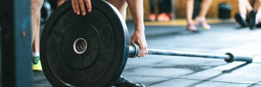 person som trener crossfit og setter på vekt på vektstang