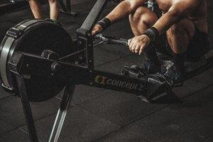 En person som trener romaskin. Har wristwraps. Maskinen er plassert på et svart gummi gulv.