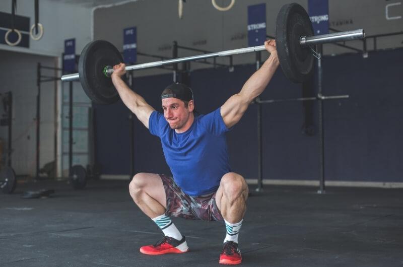 person som demostrerer overhead squats
